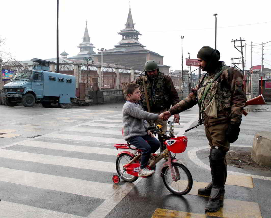 NOT THE ENEMY: A child shakes hands with a security personnel near Jamia Masjid in downtown Srinagar after curbs were imposed by the authorities in view of separatists' strike call protesting against the killing of two civilians including a woman in security force firing, UNI