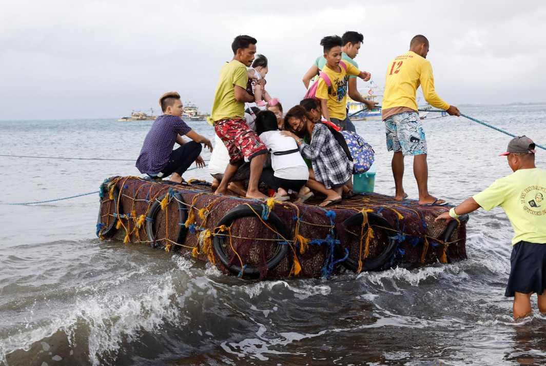 INCONVENIENCED: Stranded passengers ride on a makeshift raft after all ferry service was cancelled, a day after a Philippine vessel capsized because of bad weather in Infanta, Quezon in the Philippines, Reuters/UNI