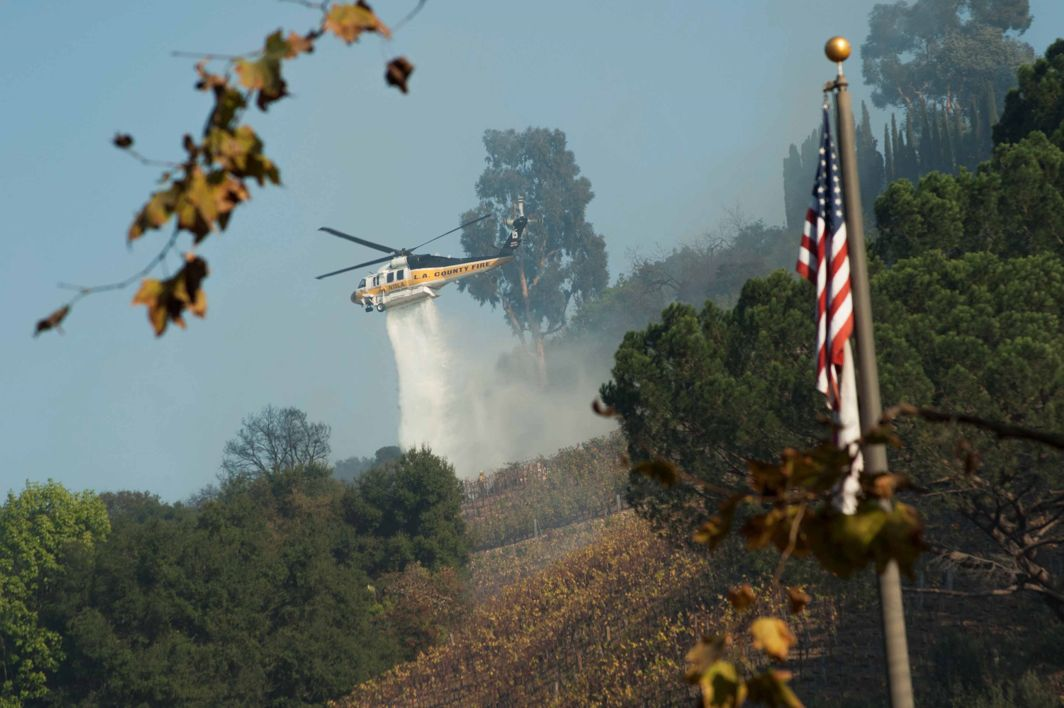 DOUSE THE BLAZE: A helicopter drops water on a vineyard owned by Rupert Murdoch damaged by the Skirball fire near the Bel Air neighborhood on the west side of Los Angeles, California, US, Reuters/UNI