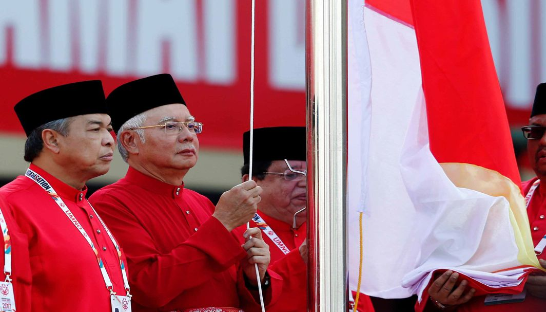 SALUTE TO THE PARTY: Malaysia's Prime Minister Najib Razak raises the United Malays National Organization (UMNO) flag beside his deputy Ahmad Zahid Hamidi during its general assembly in Kuala Lumpur, Malaysia, Reuters/UNI