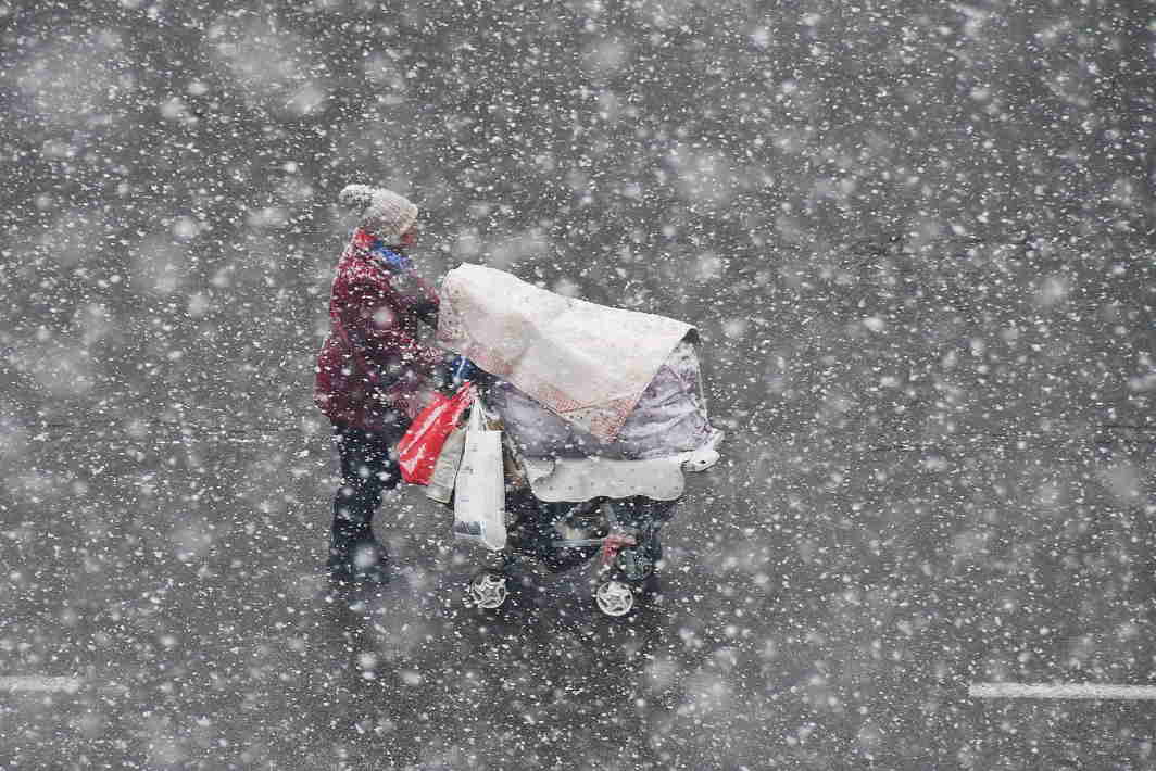MERCURY DROP: A woman pushing a stroller walks in the snow in Yantai, Shandong province, China, Reuters/UNI