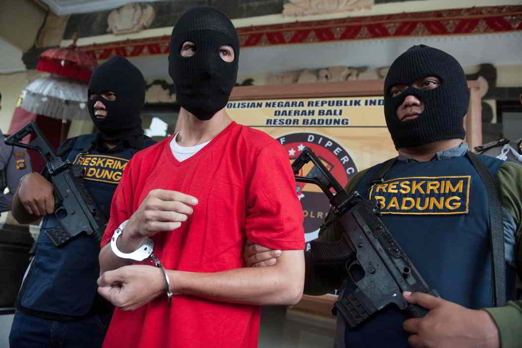 HELPLESS: Indonesian policemen hold rifles while guarding recaptured US citizen and inmate Christian Beasley, who escaped from Kerobokan Prison, at Badung police station in Denpasar, Bali, Indonesia, Nyoman Budhiana/Antara Foto/Reuters/UNI