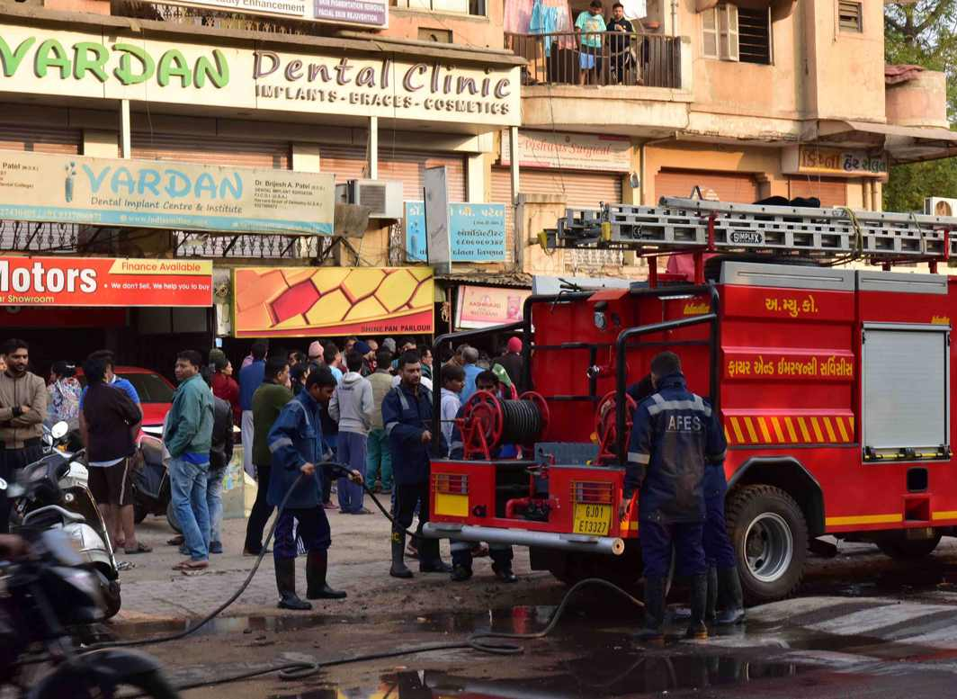TOO LITTLE TOO LATE: Firefighters prepare to douse flames after a fire broke out in a grocery store in which four members of a family were killed at the Naranapura area of Ahmedabad, UNI