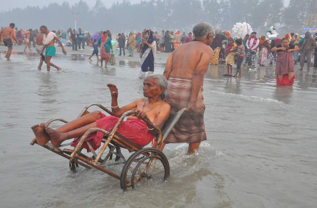 MOTHER I LOVE YOU: An elderly man helps his wheelchair-bound nonagenarian mother take a dip in the Ganga at Sagar Island, UNI
