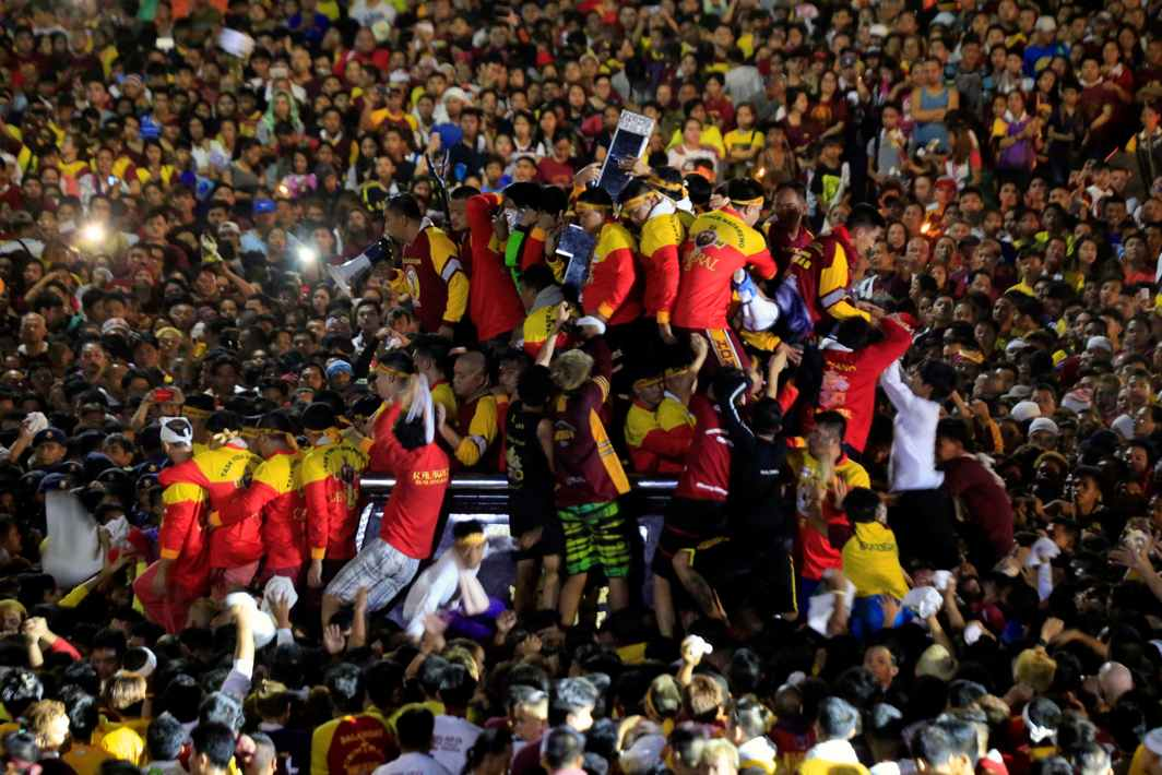 OUTPOURING: Devotees climb on a carriage to hold the image of the Black Nazarene during an annual procession at Luneta grandstand, Metro Manila, Philippines, Reuters/UNI