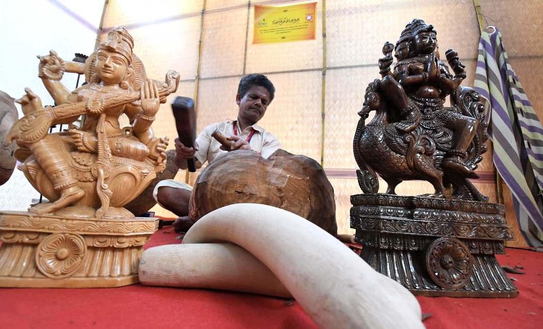 DEXTROUS HANDS: An artisan makes wooden sculptures at an exhibition in Thiruvananthapuram, UNI