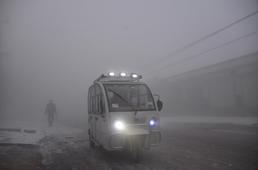 THROUGH THE HAZE: A man rides an electric tricycle amid smog in Chiping, Shandong province, China, Reuters/UNI