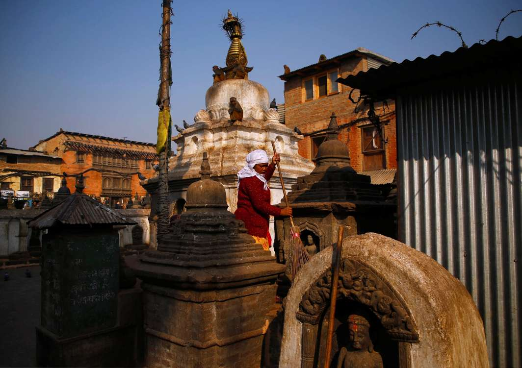 HALLOWED SOIL: A woman sweeps the premises of Swayambhunath Stupa in Kathmandu, Nepal, Reuters/UNI