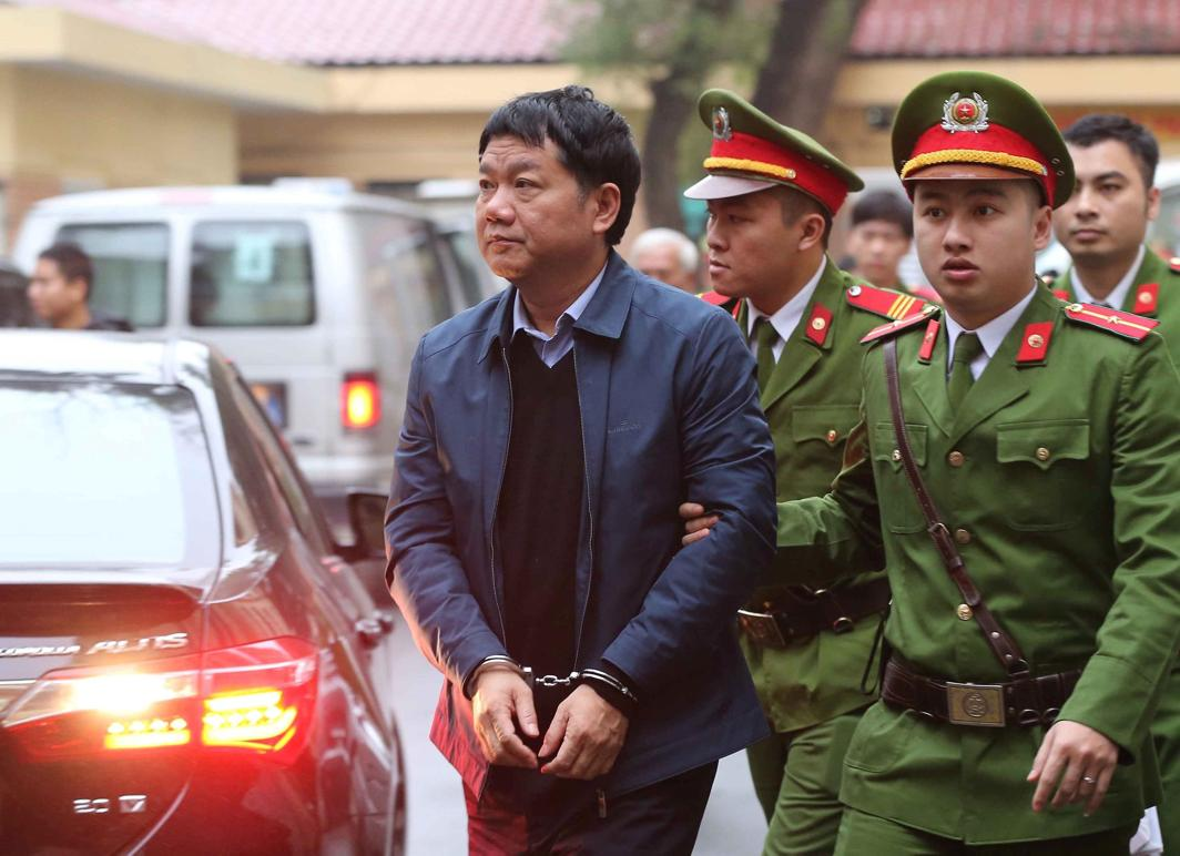 UNDER ARREST: Vietnam's Communist Party Politburo former member and former chairman of PetroVietnam Dinh La Thang (L) is escorted by police to the court in Hanoi, Vietnam, VNA/Doan Tan/Reuters/UNI