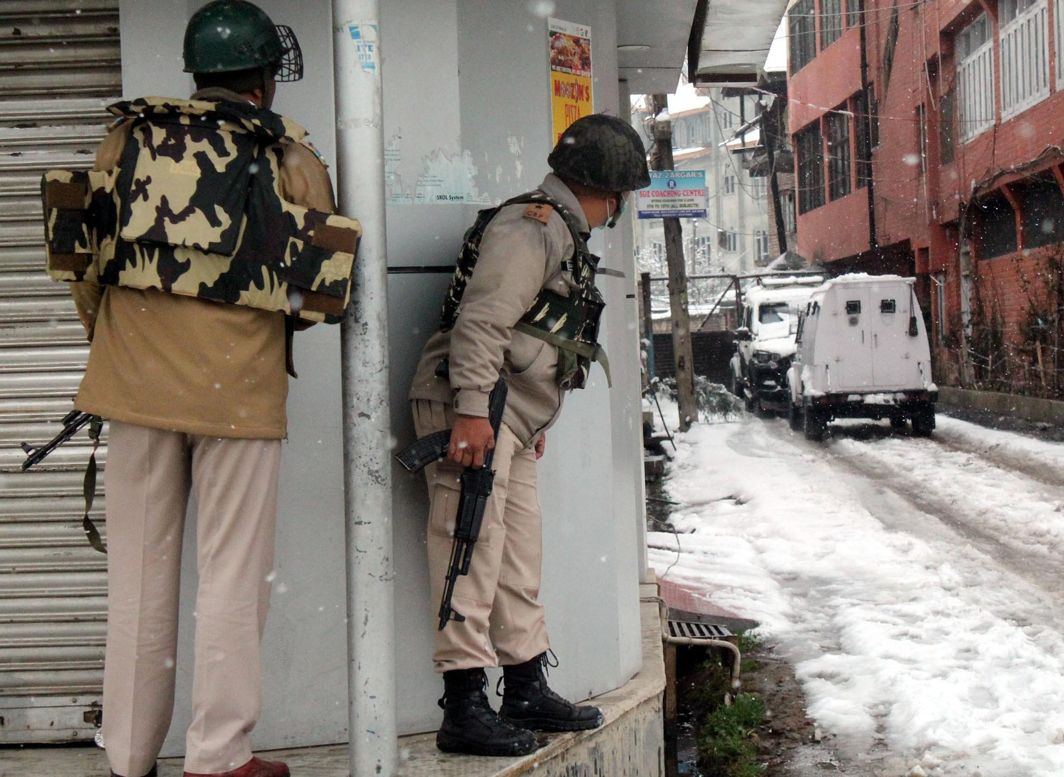 FIRING BEGINS: Security personnel take position at Karan Nagar, Srinagar where militants are holed up in a building during an encounter with the forces, UNI