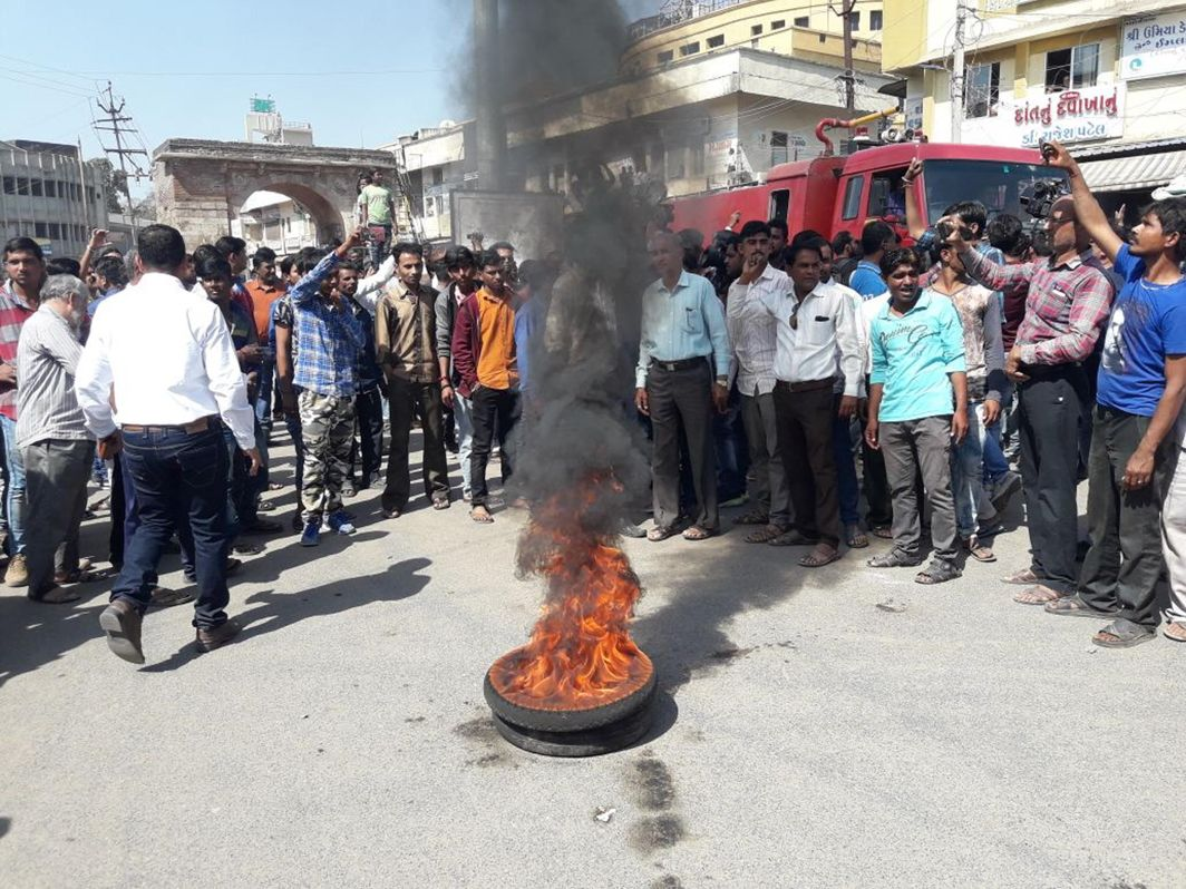 BURNING QUESTION: Members of various Dalit organisations burn tyres suspended on rods during Patan bandh, called after a Dalit activist, Bhanubhai Vankar, got injured in a self-immolation bid outside the collector's office, UNI