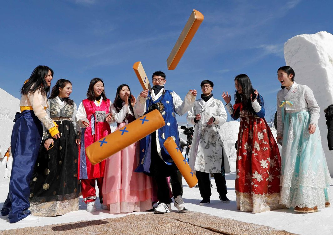 STRIKING AT THE ROOTS: People dressed in Korean ethnic costumes play a traditional game as they celebrate the Lunar New Year among ice sculptures in Pyeongchang, South Korea, Reuters/UNI