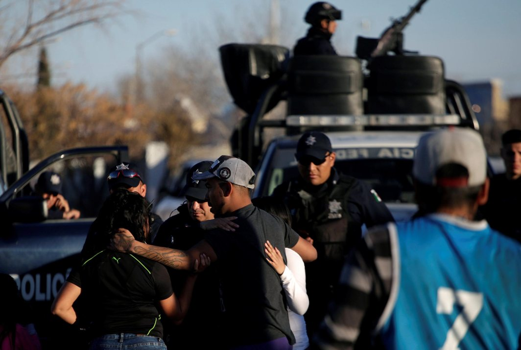 GRIEF: The relatives of a slain man embrace each other in front of federal police, where unknown assailants killed four men in a garage, according to local media, in Ciudad Juarez, Mexico, Reuters/UNI