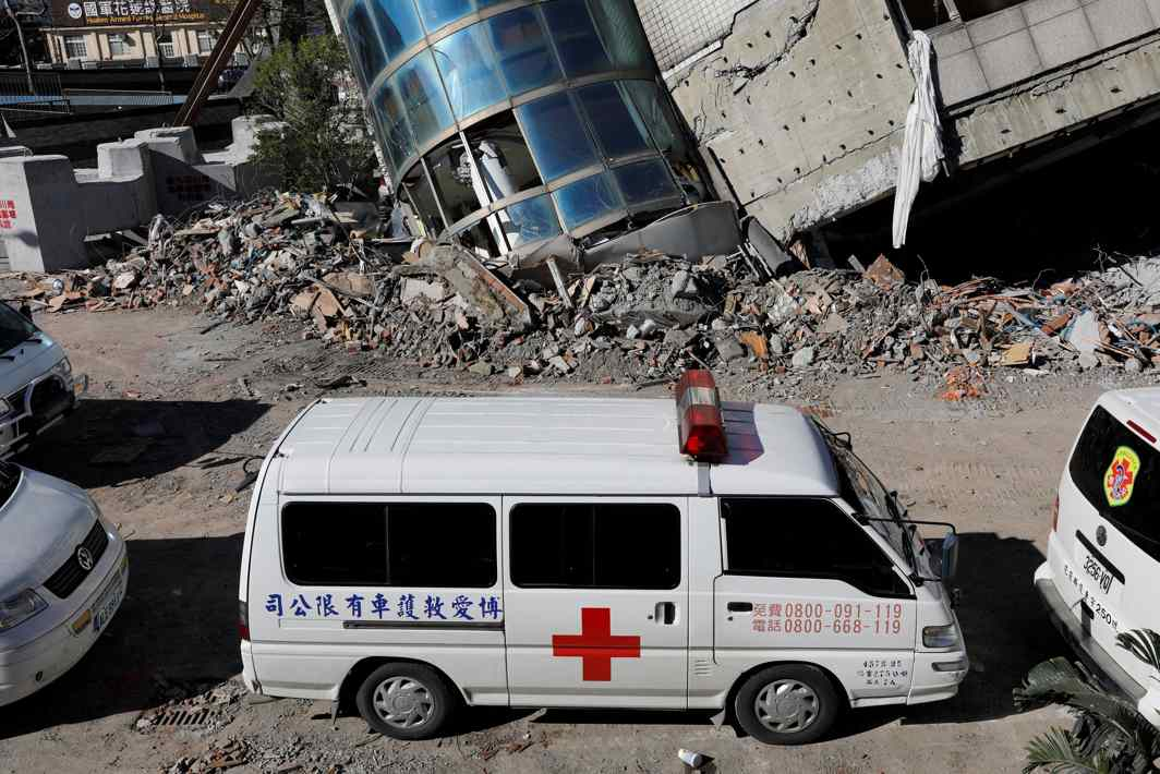 SUDDEN DESTRUCTION: Ambulances park outside a collapsed building after an earthquake hit Hualien, Taiwan, Reuters/UNI