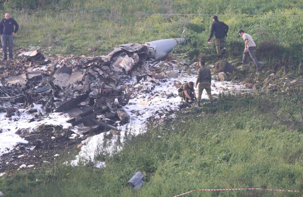COST OF WAR: Israeli security forces walk next to the remains of an F-16 Israeli war plane near the Israeli village of Harduf, Reuters/UNI