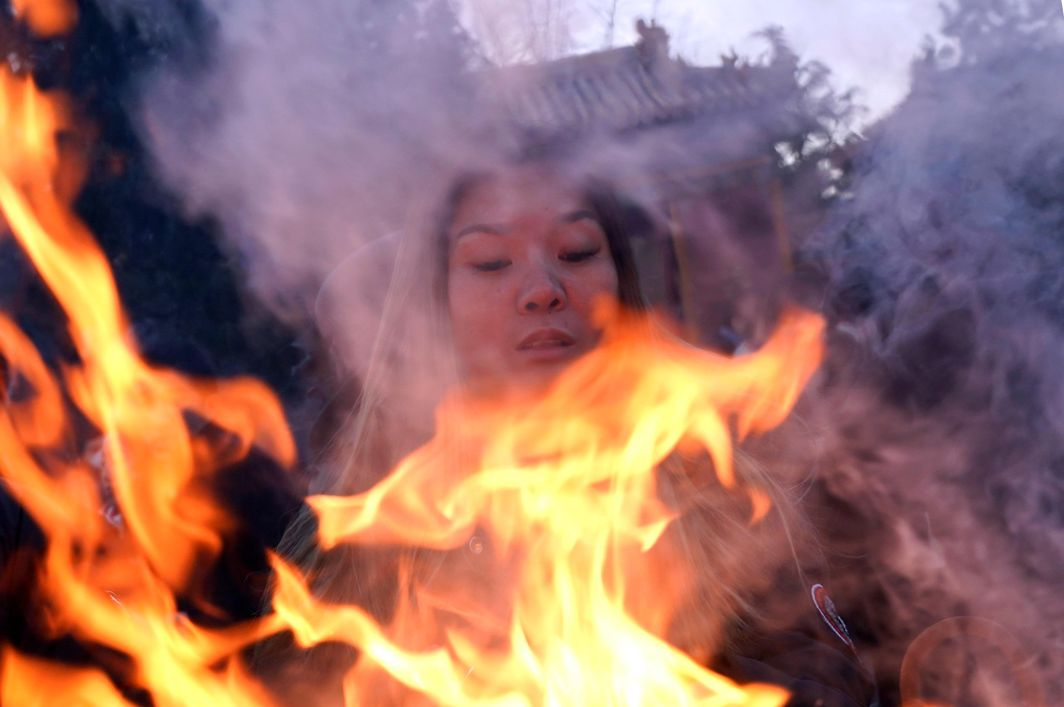 FOR AN AUSPICIOUS START: A woman burns incense to pray for good fortune at Lama Temple on the first day of the Year of the Dog in Beijing, China, Reuters/UNI