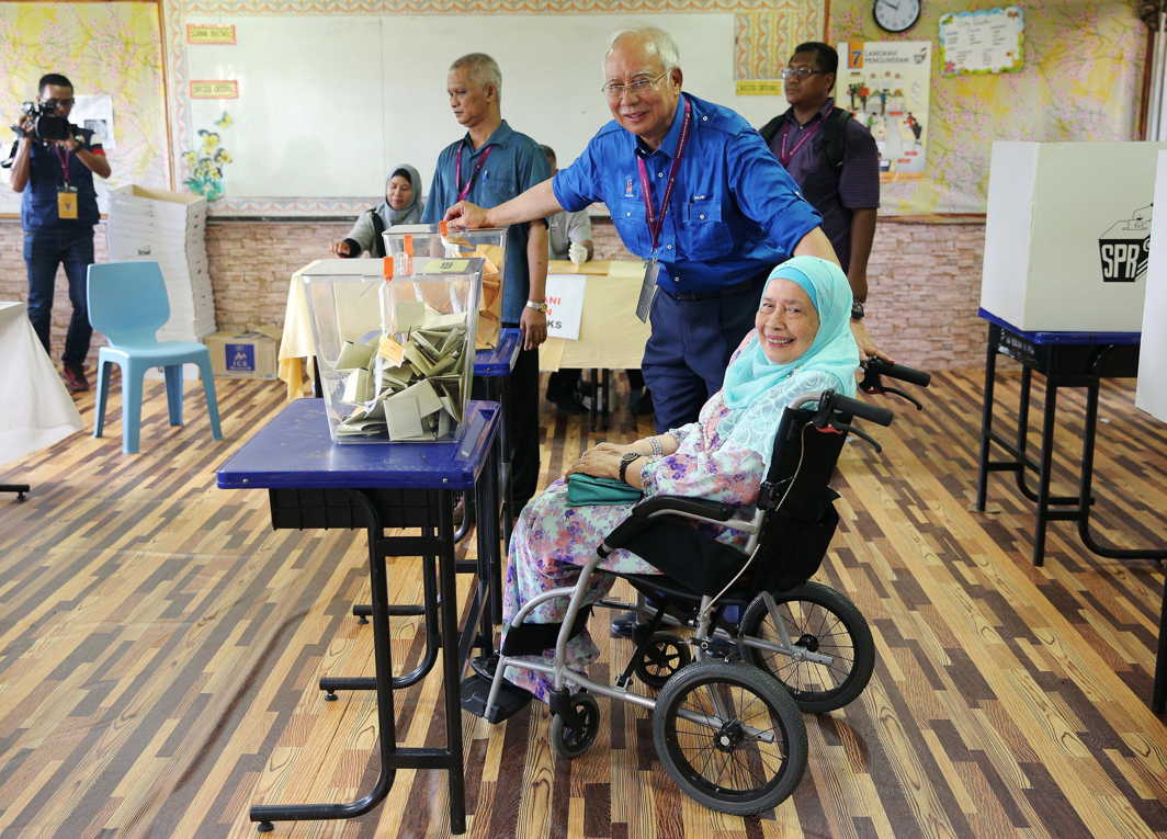 Prime Minister Najib Razak of Barisan Nasional (National Front) helps his wheelchair-bound mother Rahah Noah drop her ballot into a ballot box during Malaysia's general election in Pekan, Pahang, Malaysia, Reuters/UNI