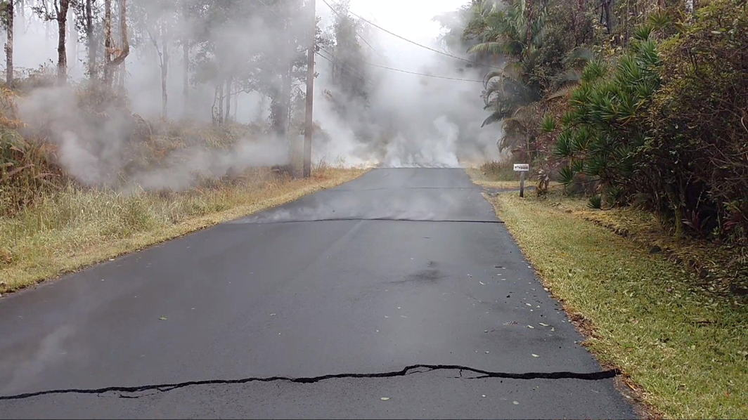 Steam rises from cracks on a road in Nohea, Hawaii, US in this still image from video taken on May 8, 2018, Apau Hawaii Tours/Social Media/Reuters/UNI