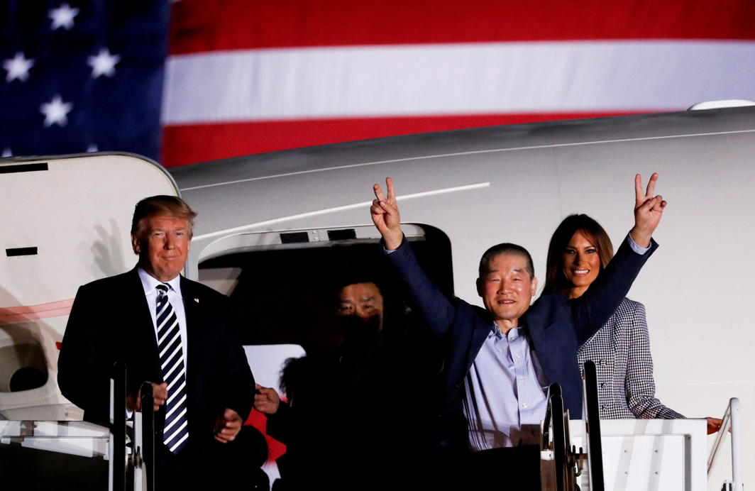 One of the Americans formerly held hostage in North Korea gestures next to US President Donald Trump and first lady Melania Trump, upon their arrival at Joint Base Andrews, Maryland, Reuters/UNI