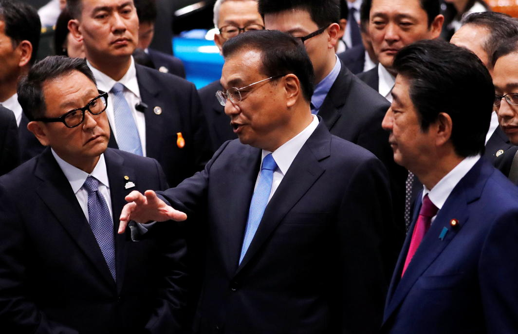 China's Premier Li Keqiang, Japan's Prime Minister Shinzo Abe and Toyota Motor Corp President Akio Toyoda talk during a visit to a plant of Toyota Motor Hokkaido, Inc in Tomakomai, on Japan's northern island of Hokkaido, Reuters/UNI