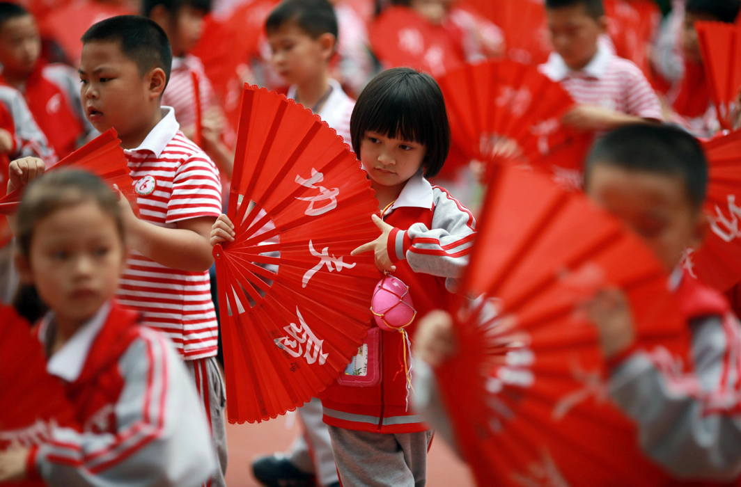 Children perform a Kung Fu Fan dance while carrying plastic eggs during the