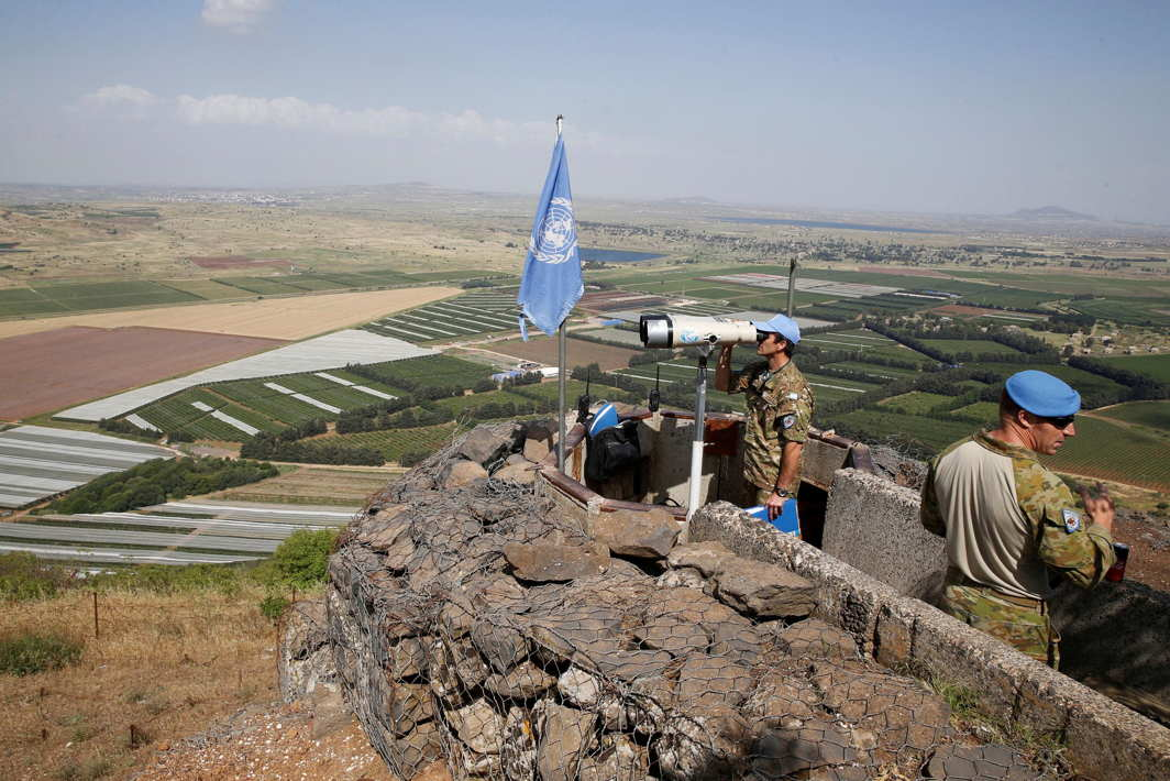 A United Nations Truce Supervision Organisation military observer uses binoculars near the border with Syria in the Israeli-occupied Golan Heights, Israel, Reuters/UNI