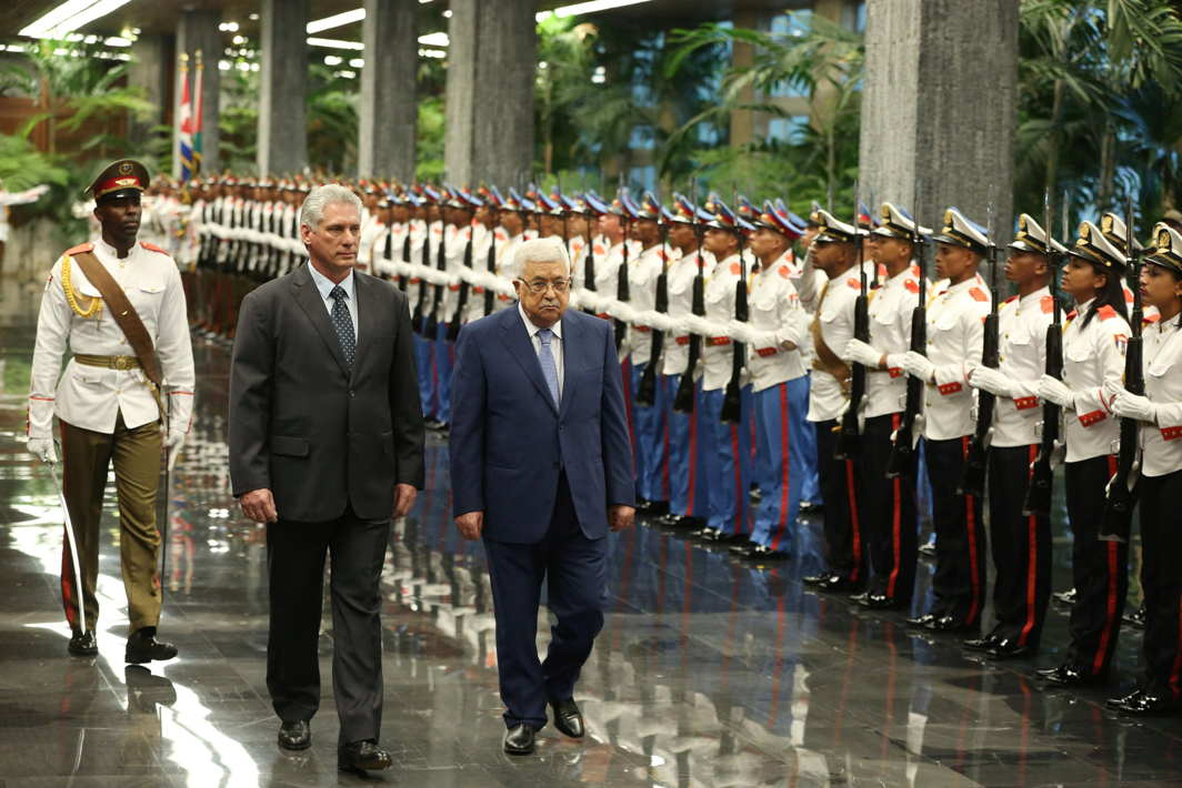 Cuban President Miguel Diaz-Canel (L) and Palestinian President Mahmoud Abbas review an honour guard during a ceremony at the Revolution Palace in Havana, Reuters/UNI
