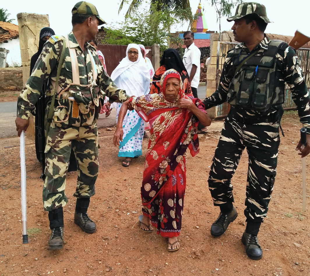 Security personnel help women at a polling booth at Yamakanamardi constituency of Karnataka, UNI