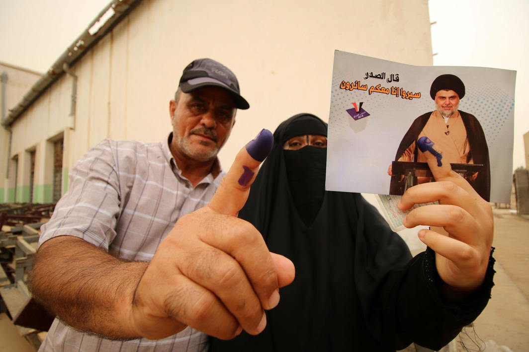 Iraqi people show their ink-stained fingers after casting their votes at a polling station during the parliamentary election in Basra, Reuters/UNI