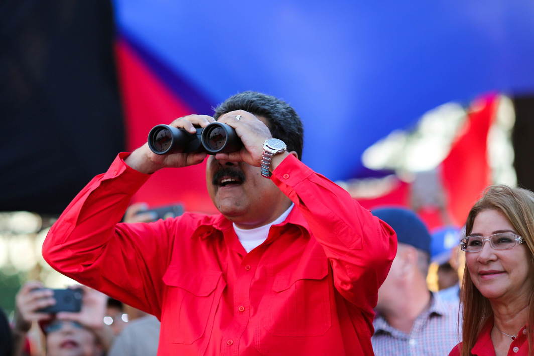 Venezuela's President Nicolas Maduro uses binoculars next to his wife Cilia Flores, during a campaign rally in Cumana, Reuters/UNI