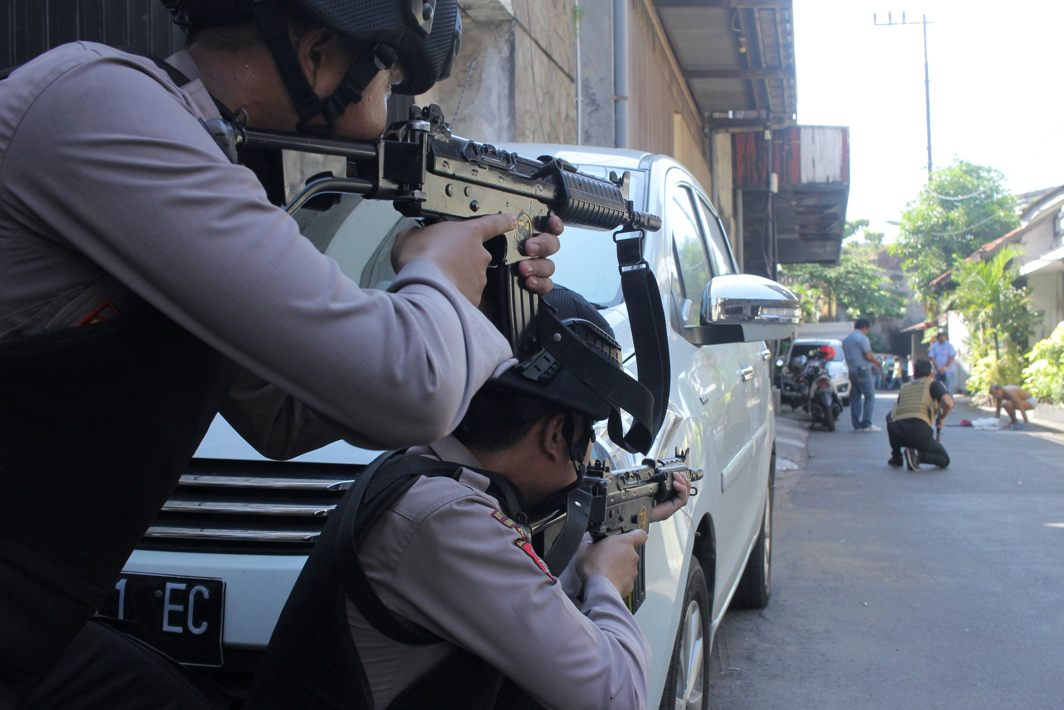 Police aim their weapons at a man who was being searched by other police officers following an explosion at nearby police headquarters in Surabaya, Indonesia, Didik Suhartono/Antara Photo/Reuters/UNI