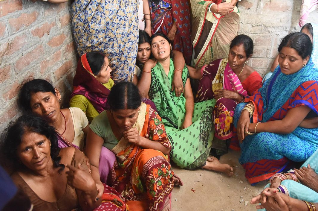 Relatives of a man who died as a wall collapsed in a storm, mourn his death in Patna, UNI