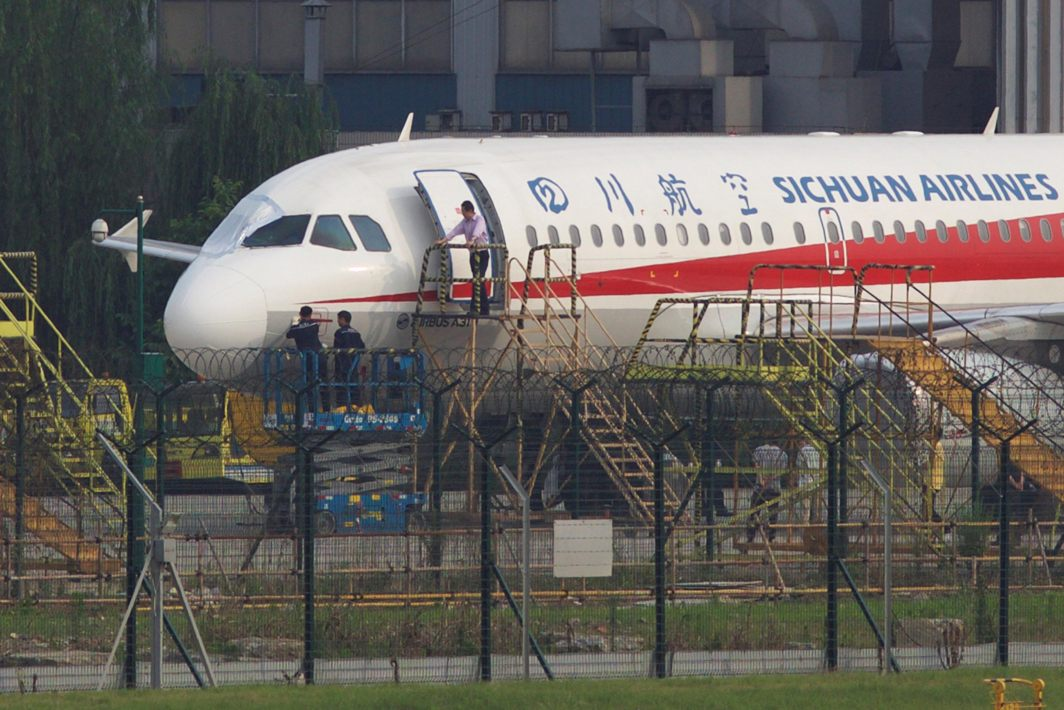 Workers inspect a Sichuan Airlines aircraft that made an emergency landing after a windshield on the cockpit broke off, at an airport in Chengdu, Sichuan province, China, Reuters/UNI