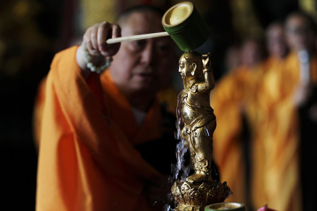 A monk pours water over a Buddha statue to mark Buddha's birthday at Yuantong temple in Kunming, Yunnan province, China, Reuters/UNI