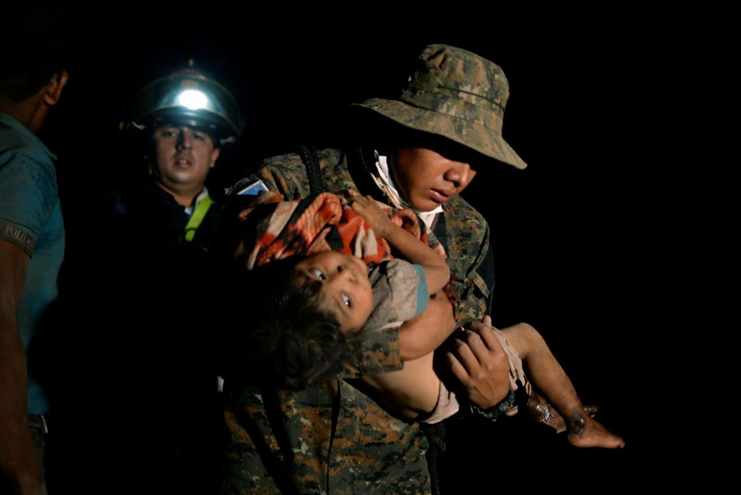 A soldier carries a child covered in ash after Guatemala's Fuego volcano erupted violently in El Rodeo, Guatemala, Reuters/UNI