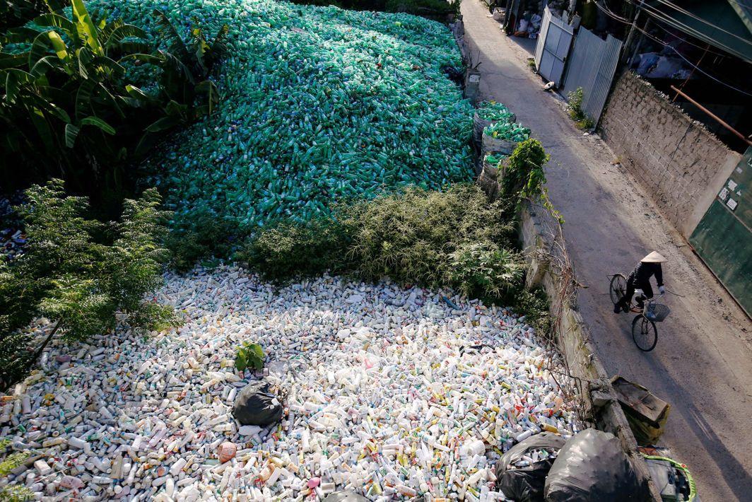 A Vietnamese woman cycles past recyclable plastic bottles at Xa Cau village, outside Hanoi, Vietnam, Reuters/UNI