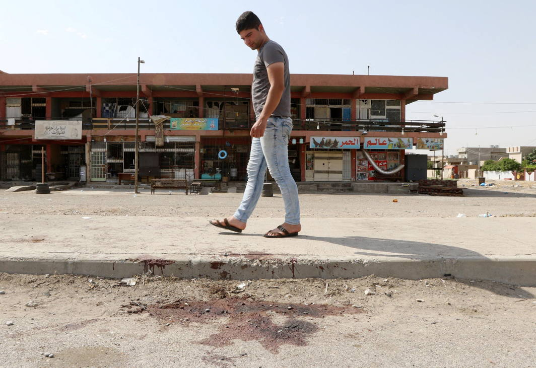 A man looks at bloodstains on a roadway after a bomb explosion in the ethnically-mixed Iraqi oil city of Kirkuk, Iraq, Reuters/UNI