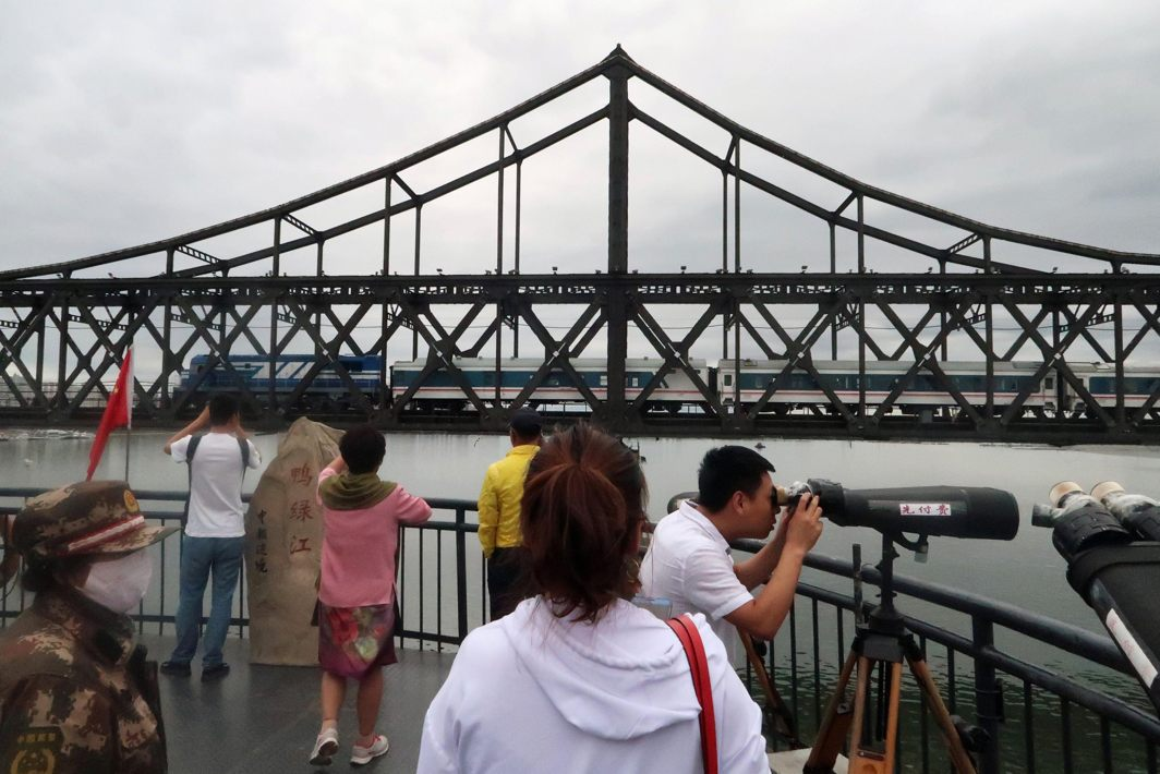 Chinese visitors look on from the Broken Bridge as a train travels on the Friendship Bridge across the Yalu river from North Korea to China, in Dandong, Liaoning province, China, Reuters/UNI