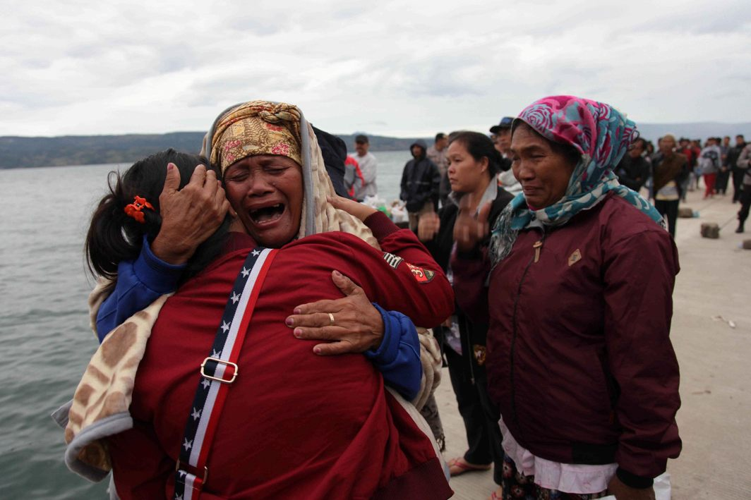 Relatives cry while waiting for news on missing family members who were on a ferry that sank yesterday in Lake Toba, at Tigaras Port, Simalungun, North Sumatra, Indonesia, Reuters/UNI