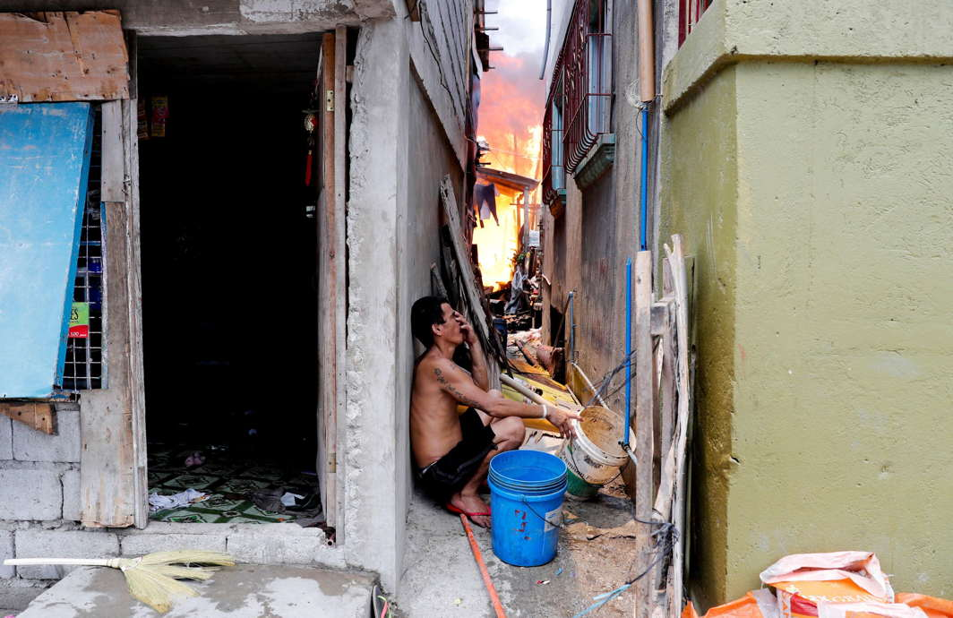 A man sits in a narrow alley as his house burns in Muntinlupa, Metro Manila, Philippines, Reuters/UNI