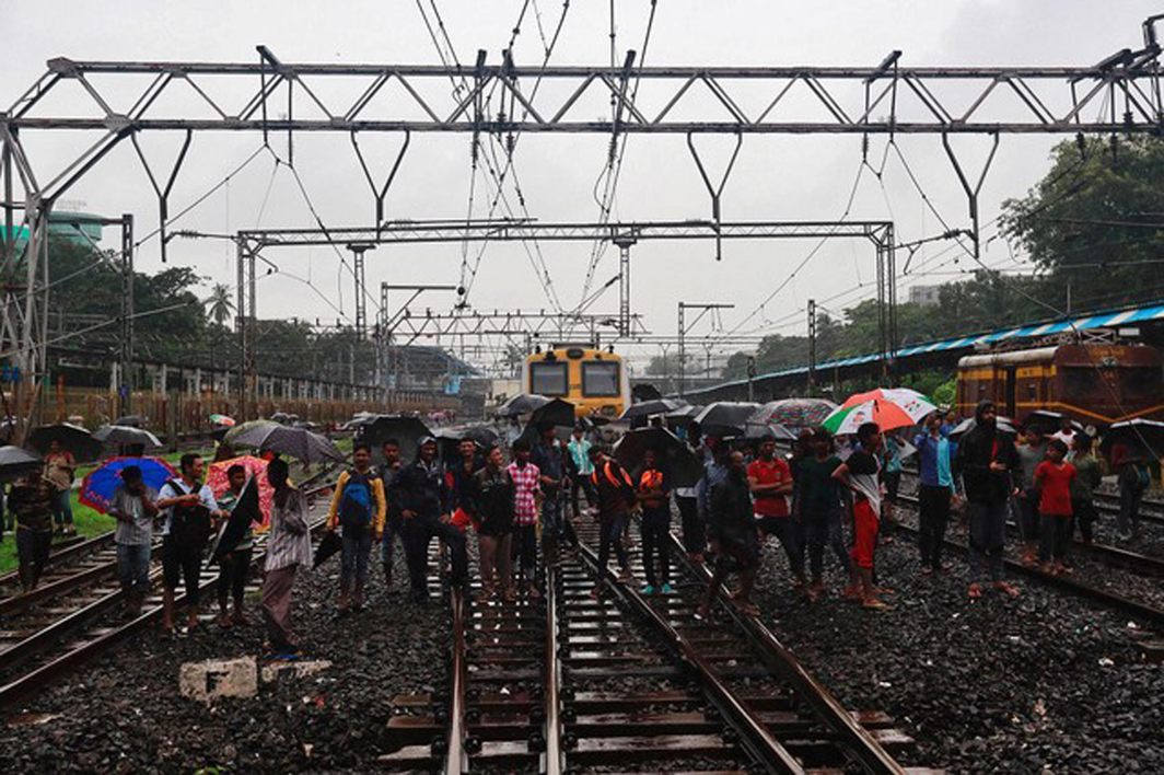 Commuters watch the rescue work at the site of an overbridge that collapsed over railway tracks after heavy rains in Mumbai, Reuters/UNI