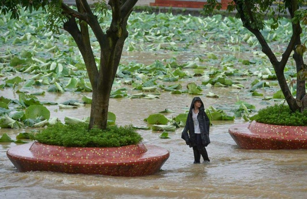 A boy stands on a flooded road amid heavy rainfall in Chengdu, Sichuan province, China, Reuters/UNI