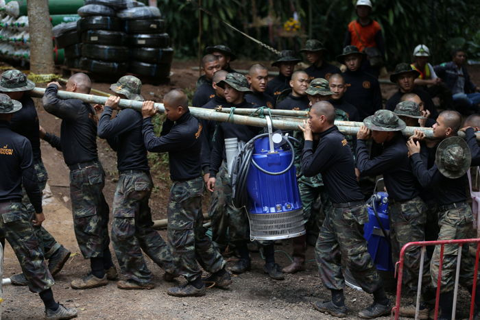 Military personnel carry a water pump machine as they enter the Tham Luang cave complex, where 12 boys and their soccer coach are trapped, in the northern province of Chiang Rai, Thailand, Reuters/UNI