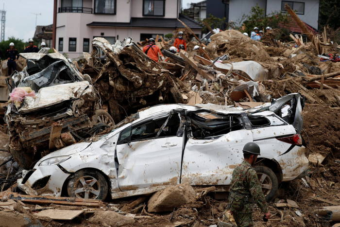 Rescue workers conduct search and rescue operations at a landslide site caused by heavy rain in Kumano Town, Hiroshima Prefecture, western Japan, Reuters/UNI