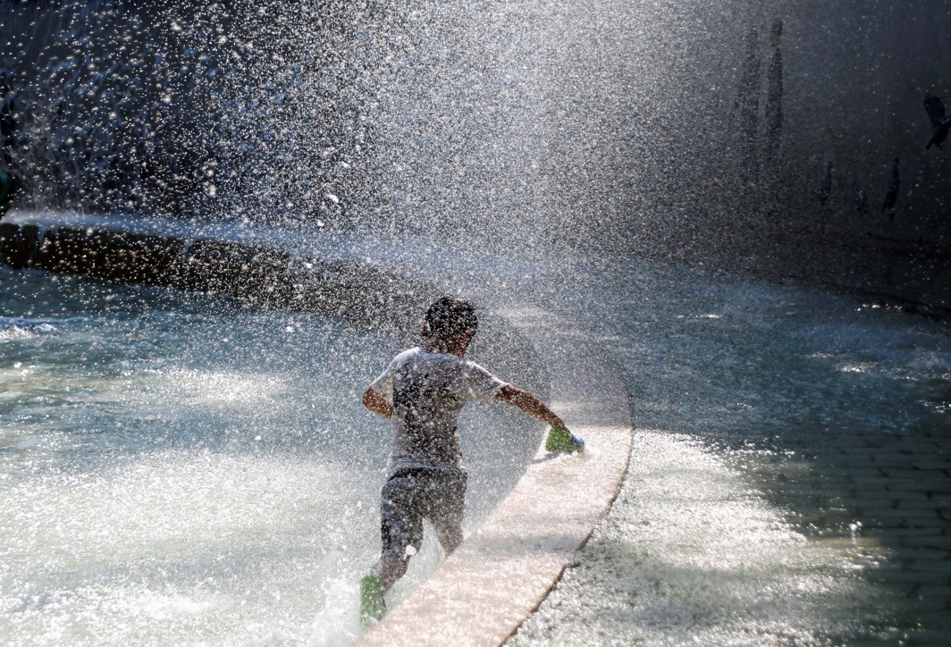 A boy plays in a fountain to cool down at a park during a hot summer day in Tokyo, Japan, Reuters/UNI