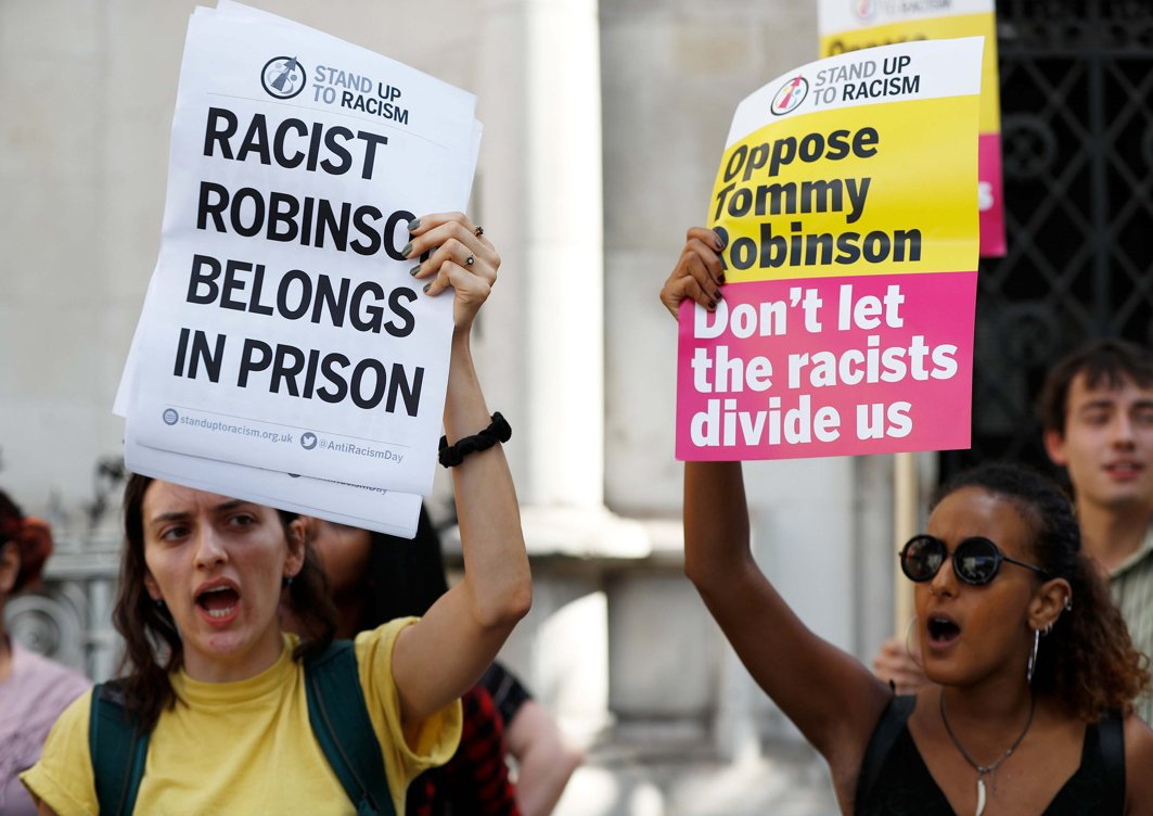 Protesters hold up placards outside the High Court during an appeal by former English Defense League leader Tommy Robinson, whose real name is Christopher Yaxley-Lennon, against his conviction and jailing for contempt of court, in London, Britain, Reuters/UNI
