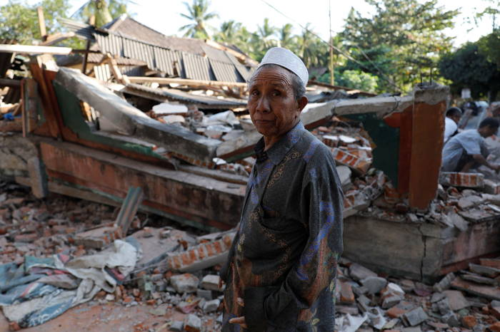 A villager walks through a collapsed house after an earthquake hit Lombok Island in Pemenang, Indonesia, Reuters/UNI