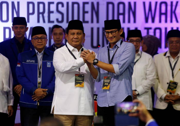 Former general and head of the Gerindra Party Prabowo Subianto (L) and his running mate former Jakarta vice-governor Sandiaga Uno shake hands along with coalition party heads after they register as candidates for the 2019 presidential election at the General Election Commission, Reuters/UNI