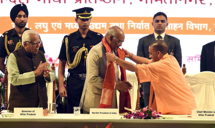 President Ram Nath Kovind is welcomed by Chief Minister Yogi Adityanath during inauguration of the One District One Product Summit as Uttar Pradesh Governor Ram Naik looks on, in Lucknow, UNI