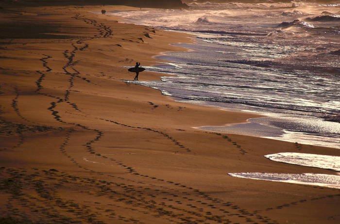 People walk along the beach as a surfer holding his board looks at the waves on Merewether Beach in Newcastle, located north of Sydney, Australia, Reuters/UNI
